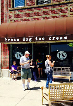 People eat ice cream outside underneath a brown awning with the text: brown dog ice cream.