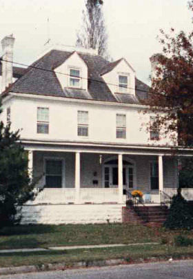 The front of the Inn with its gray roof, white siding and large, wraparound porch.
