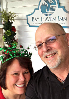 The Innkeepers, Tammy and Jim, smile underneath a sign with the text: Bay Haven Inn of Cape Charles.
