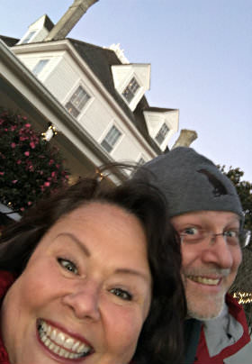 The Innkeepers, Tammy and Jim, smile with the stately white-sided Inn behind them.