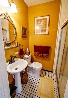 A white porcelain toilet and sink in a bathroom with yellow walls and black and white tiled floor.
