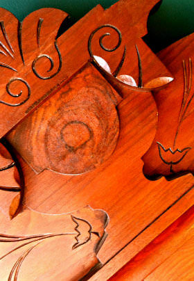 A rich, warm piece of wooden furniture is carved with flower and leaf patterns.
