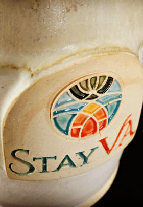 A beige mug with a blue, orange and green glazed logo and the text: STAY VA.