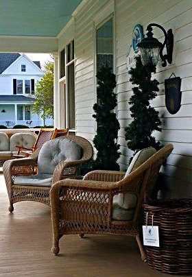 Two wicker chairs with light blue cushions sit before two decorative pines on the front porch of the Inn.