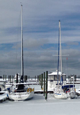 Two sailboats rest at the dock with a fine layer of white snow on the iced over Bay.