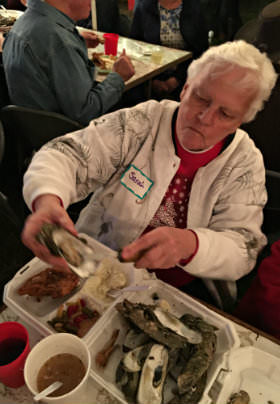 A woman in a white coat pulls an oyster from her container of oysters at a table.