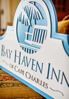 A blue and white wooden sign with the text: Bay Haven Inn of Cape Charles.