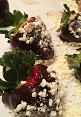 Dark chocolate covered strawberries with green leaves sit in crumbled, white sugar.