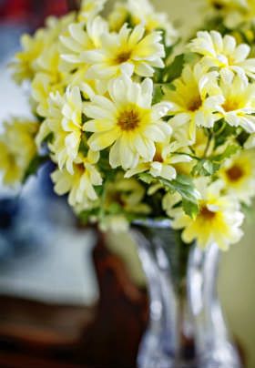 A bouquet of white and yellow flowers rests in a tall, glass vase on a brown wooden table.