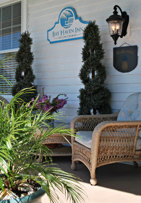 Two wicker chairs with light blue cushions sit on the front porch with a green potted palm before them.