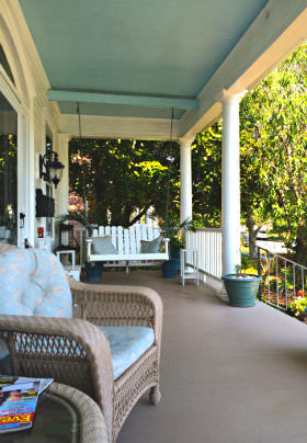 A wicker chair with a light blue cushion sits on the deck of the front porch with a white wooden rocker in the background.