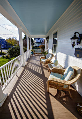 Two wicker chairs with light blue cushions sit on the front porch with shadows coming through the white railing.
