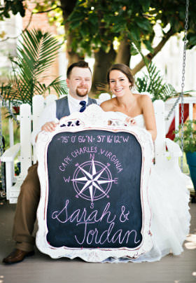 A newly married couple sits on a white wooden rocker holding a sign with the text: Cape Charles, Virginia, Sarah & Jordan.