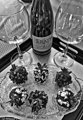 A plate of six chocolate covered strawberries on a serving tray with a bottle of wine and two wine glasses.