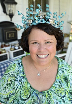 Tammy, the Innkeeper, smiling, wearing an ornate blue tiara and a green patterned blouse.