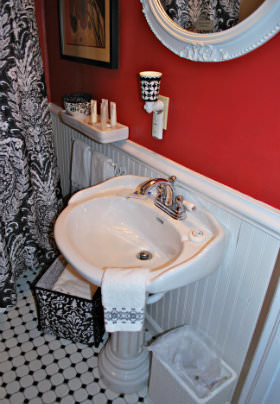 A white porcelain sink below a white trimmed mirror on a red and white wall.
