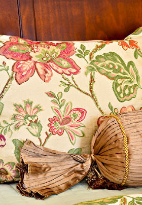 A beige pillow with a red and green floral print before a brown wood paneled wall.
